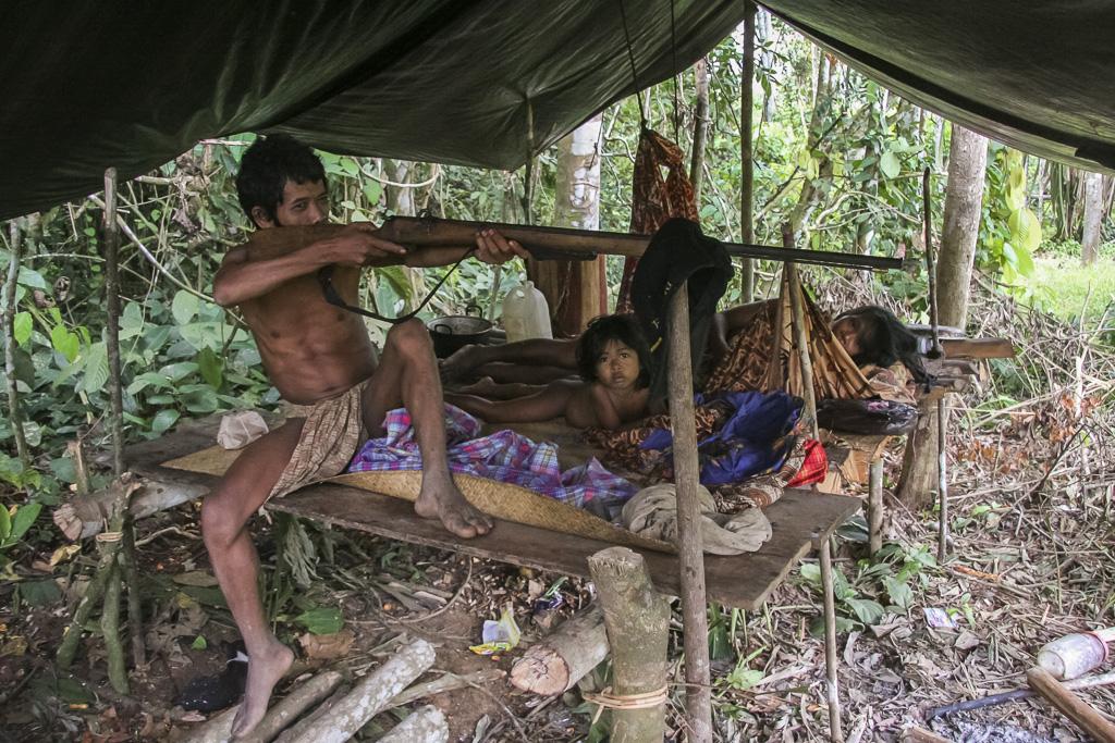 Orang rimba family at hut, Head of family pose proudly showing his shotgun. Jungle Area of Bukit Duabelas National Park. Jambi province. Sumatra. Indonesia.