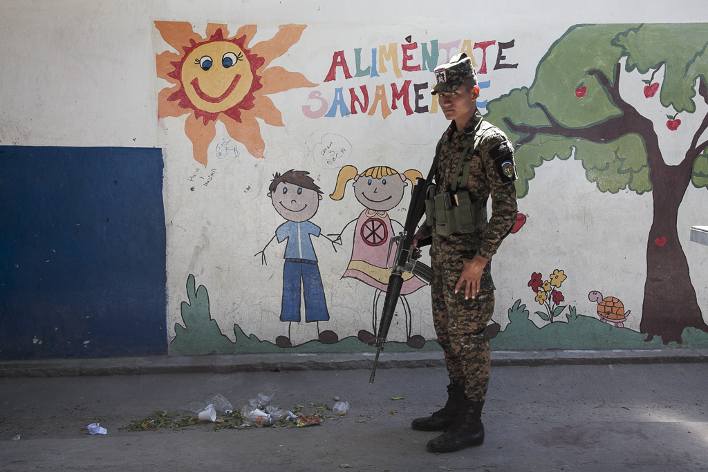 A soldier stands guard during an event in a public school of the city suburbs. San Antonio. San Salvador.