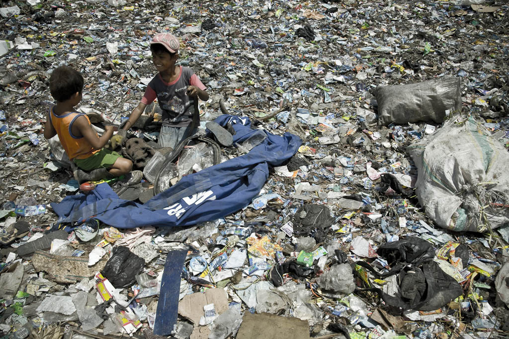 Two kids turn over the garbage looking for plastic or another valued material. Makkasar dump. Indonesia.