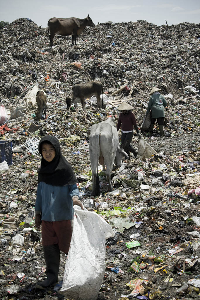 A girl armed with a hook faces up the day unwillingly. Makkasar dump. Indonesia.