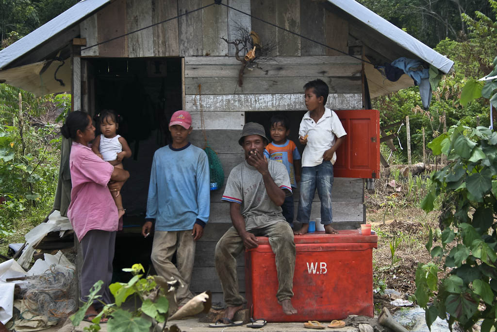 A fisherman with his family in their house built from the tsunami ruins. One year after 2004 December 26 tsunami reportage. Sampoinet, Aceh province, Sumatra, Indonesia.