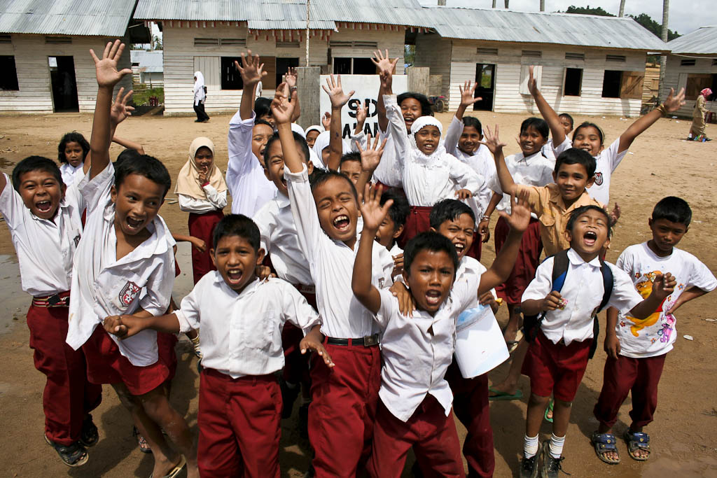 Children jump cheerfully in the temporary schools of Calang one year after the December 2004 Tsunami in Aceh province, Sumatra, Indonesia. After the big waves, many people from surrounding villages came to live to this town where they could find basic infrastructures that were destroyed in their hometowns. One year after 2004 December 26 tsunami reportage. Calang, Aceh province, Sumatra, Indonesia.
